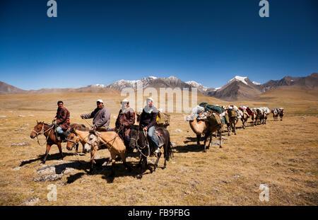 Four nomad guides (Hogshin, Kishgee, Idesh and Tsaganaa) lead a camel-train over the Kharkhiraa mountain pass, Mongolia. - Stock Photo