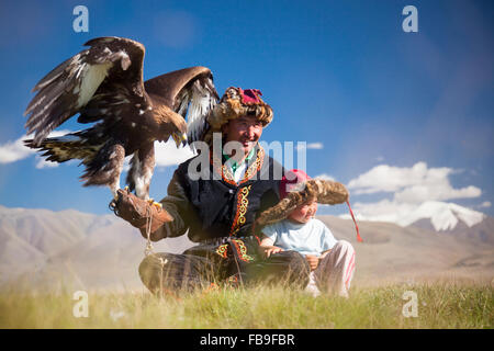 A Kazakh eagle hunter and son in the Tsaast Uul Valley, far-western Mongolia. - Stock Photo