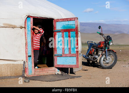A girl pokes her head out of her family ger tent in the Tsaast Uul Valley in remote western Mongolia. - Stock Photo