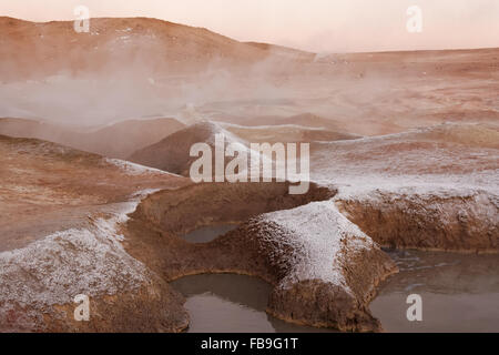 early morning view of the smoking craters in a lunar type landscape in Bolivia South America - Stock Photo