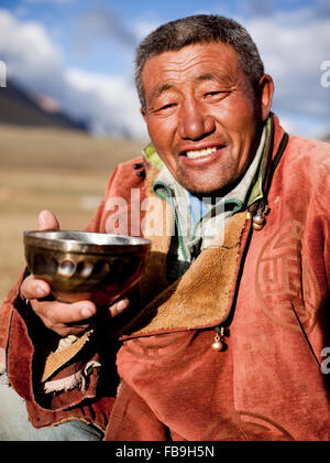 Idesh, a local herder and guide, rests with a hot tea in Kharkhiraa Turgen National Park, Mongolia. - Stock Photo