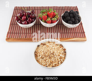 Homemade Granola and Cherries, Strawberries, and Blackberries in ceramic bowls on bamboo mat in the background - Stock Photo