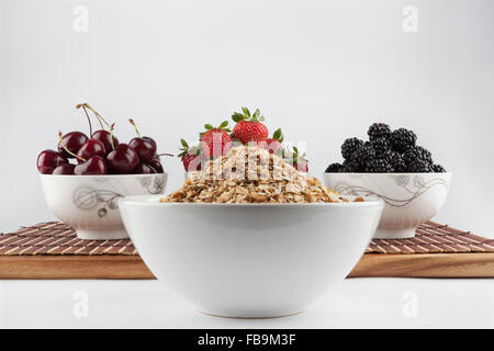 Closeup of homemade Granola and Cherries, Strawberries, and Blackberries in ceramic bowls on bamboo mat in the background - Stock Photo