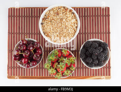 Homemade Granola and Cherries, Strawberries, and Blackberries in ceramic bowls placed on bamboo mat, isolated on - Stock Photo