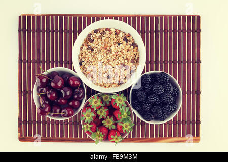 Homemade Granola and Cherries, Strawberries, and Blackberries in ceramic bowls placed on bamboo mat. Image has vintage - Stock Photo