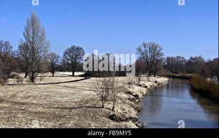 earl spring landscape in CHKO Poodri with meadow, isolated trees without leaves, Odra river and clear sky near Ostrava - Stock Photo