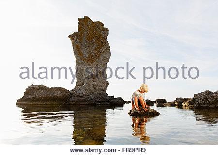 Sweden, Gotland, Faro, Blonde little boy (2-3) sitting on rock at Baltic Sea - Stock Photo