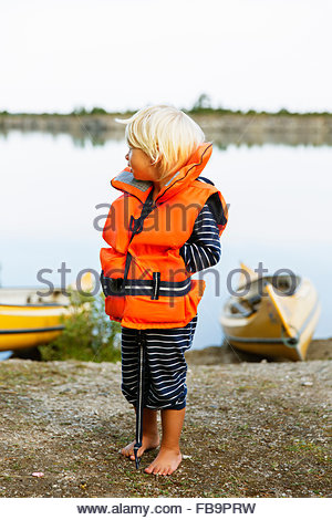 Sweden, Gotland, Farosund, Little blonde boy (2-3) wearing lifejacket standing on riverbank - Stock Photo