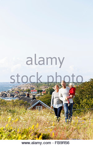 Sweden, Stockholm Archipelago, Sodermanland, Oja, Woman and man walking through meadow carrying son (2-3) on hands - Stock Photo