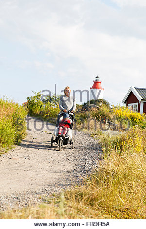 Sweden, Stockholm Archipelago, Sodermanland, Oja, Woman walking along dirt road with son (2-3) in baby carriage - Stock Photo