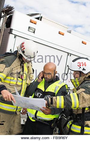 Sweden, Sodermanland, Security guard and firefighters looking at plan - Stock Photo