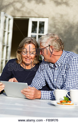 Sweden, Sodermanland, Senior couple discussing finances using digital tablet at table in backyard - Stock Photo