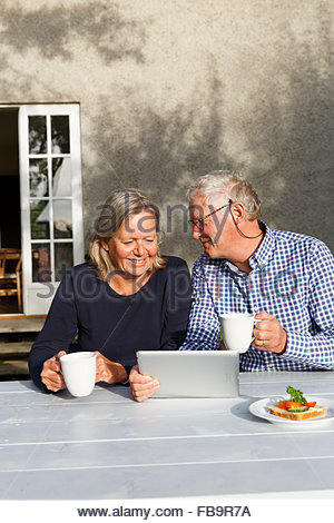 Sweden, Sodermanland, Senior couple doing financial planning using digital tablet at table in backyard - Stock Photo