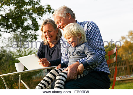 Sweden, Sodermanland, Senior couple sitting with grandson (2-3) at table using digital tablet - Stock Photo