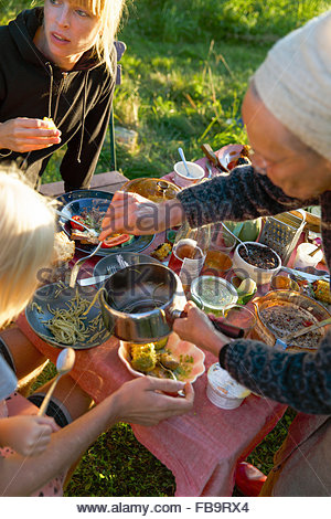 Sweden, Sodermanland, Jarna, Family with small child (4-5) having dinner in backyard at sunset - Stock Photo
