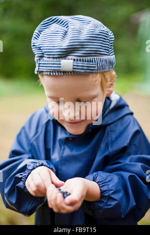 Sweden, Sodermanland, Stockholm Archipelago, Musko, Boy (4-5) with handful of bilberries - Stock Photo