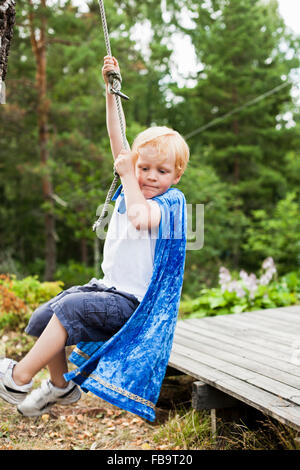 Sweden, Sodermanland, Stockholm Archipelago, Musko, Boy (4-5) swinging on rope - Stock Photo