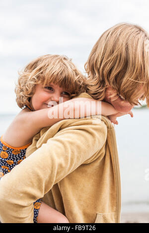 Sweden, Sodermanland, Stockholm Archipelago, Musko, Daughter (4-5) embracing mother - Stock Photo