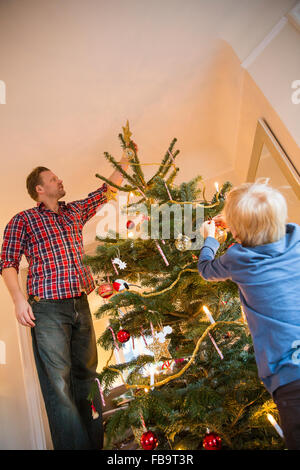 Sweden, Father and son (4-5) decorating Christmas tree - Stock Photo