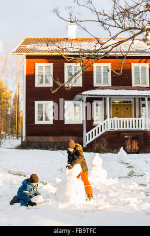 USA, Dalarna, Jarvso, Children (4-5, 6-7) playing with snowman in front of house - Stock Photo