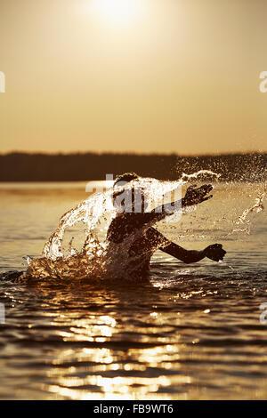 Sweden, Vastra Gotaland, Skagern, Boy (10-11) splashing in lake at sunset - Stock Photo