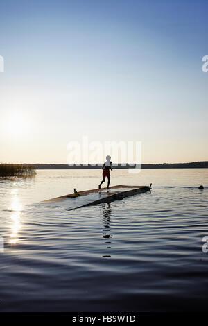 Sweden, Vastra Gotaland, Skagern, Children (6-7, 10-11) swimming in lake - Stock Photo