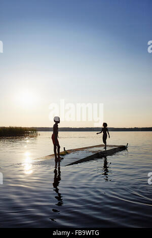 Sweden, Vastra Gotaland, Skagern, Children (6-7, 10-11) swimming in lake - Stock Photo