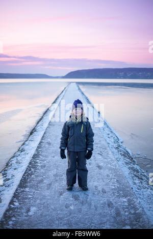 Sweden, Vastergotland, Lerum, Portrait of boy (6-7) on footbridge - Stock Photo