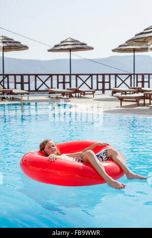 Greece, Karpathos, Amopi, Boy (8-9) lying on inflatable wheel - Stock Photo