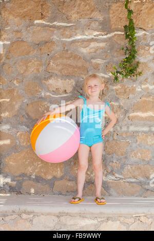 Greece, Karpathos, Amopi, Girl (6-7) standing with ball - Stock Photo
