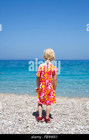 Greece, Karpathos, Amopi, Girl (6-7) standing on beach - Stock Photo