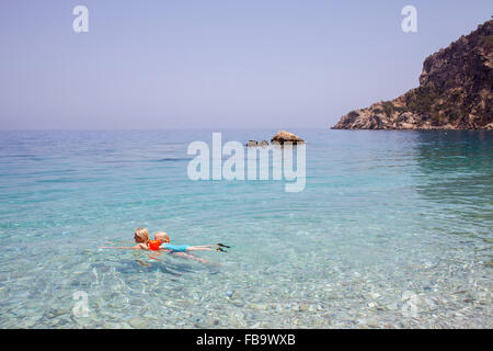 Greece, Karpathos, Amopi, Woman and girl (6-7) swimming in sea - Stock Photo