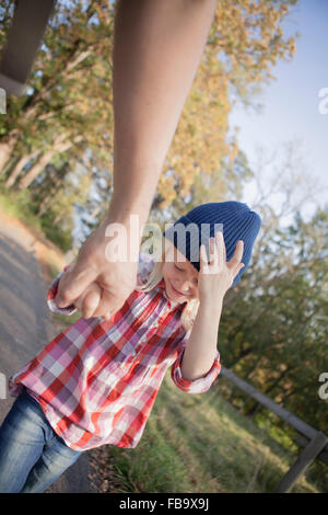 Sweden, Vastergotland, Lerum, View of father and daughter (8-9) walking on dirt road near Aspen lake - Stock Photo