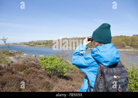 Sweden, Gothenburg Archipelago, Vastergotland, Styrso, Boy (10-11) with backpack photographing river - Stock Photo