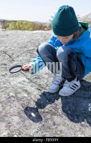 Sweden, Gothenburg Archipelago, Vastergotland, Styrso, Boy (10-11) with magnifying glass looking at rock - Stock Photo
