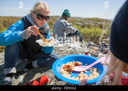 Sweden, Gothenburg Archipelago, Vastergotland, Styrso, Mom and her two kids (8-9, 10-11) eating pasta and camping - Stock Photo