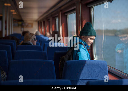 Sweden, Gothenburg Archipelago, Vastergotland, Styrso, Boy (10-11) looking through train window - Stock Photo