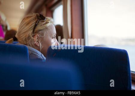 Sweden, Gothenburg Archipelago, Vastergotland, Styrso, Mature blonde woman looking through train window