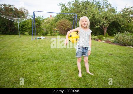 Sweden, Vastergotland, Lerum, Portrait of girl (8-9) with soccer ball standing in backyard - Stock Photo