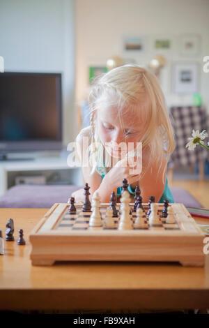 Sweden, Vastergotland, Lerum, Girl (8-9) playing chess in living room - Stock Photo