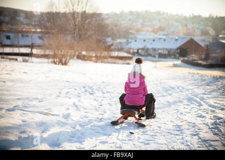 Sweden, Vastergotland, Lerum, Rear view of girl (8-9) sledding along snowy road with townscape in background - Stock Photo