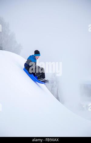 Sweden, Varmland, Sunne, Boy (12-13) sledding down snowy hill - Stock Photo