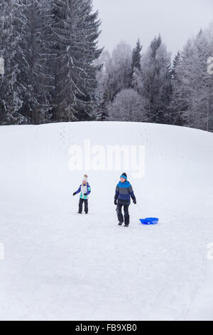 Sweden, Varmland, Sunne, Children (10-11, 12-13) playing on snowy hill - Stock Photo