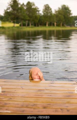 Sweden, Smaland, Braarpasjon, Girl (10-11) in lake drying off eyes with hand - Stock Photo
