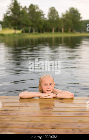 Sweden, Smaland, Braarpasjon, Portrait of girl (10-11) in lake with hands on chin - Stock Photo