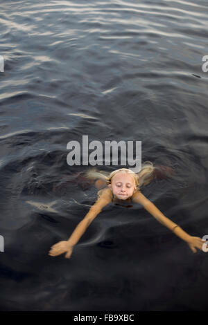 Sweden, Smaland, Braarpasjon, Girl (10-11) swimming in lake - Stock Photo