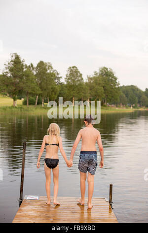 Sweden, Smaland, Braarpasjon, Girl (10-11) and boy (12-13) standing on edge of jetty - Stock Photo
