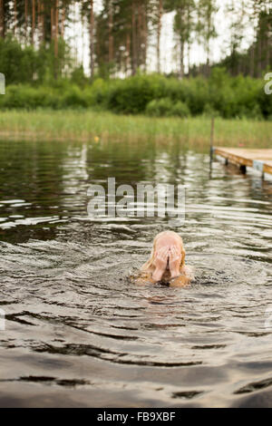 Sweden, Smaland, Braarpasjon, Girl (10-11) in lake drying off eyes with hands - Stock Photo