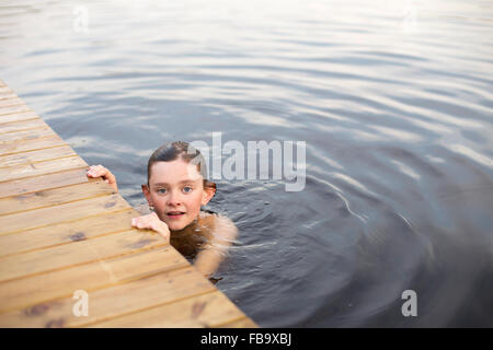 Sweden, Smaland, Braarpasjon, Portrait of boy (12-13) in lake touching wooden jetty - Stock Photo