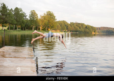 Sweden, Smaland, Braarpasjon, Boy (12-13) jumping into lake from jetty - Stock Photo